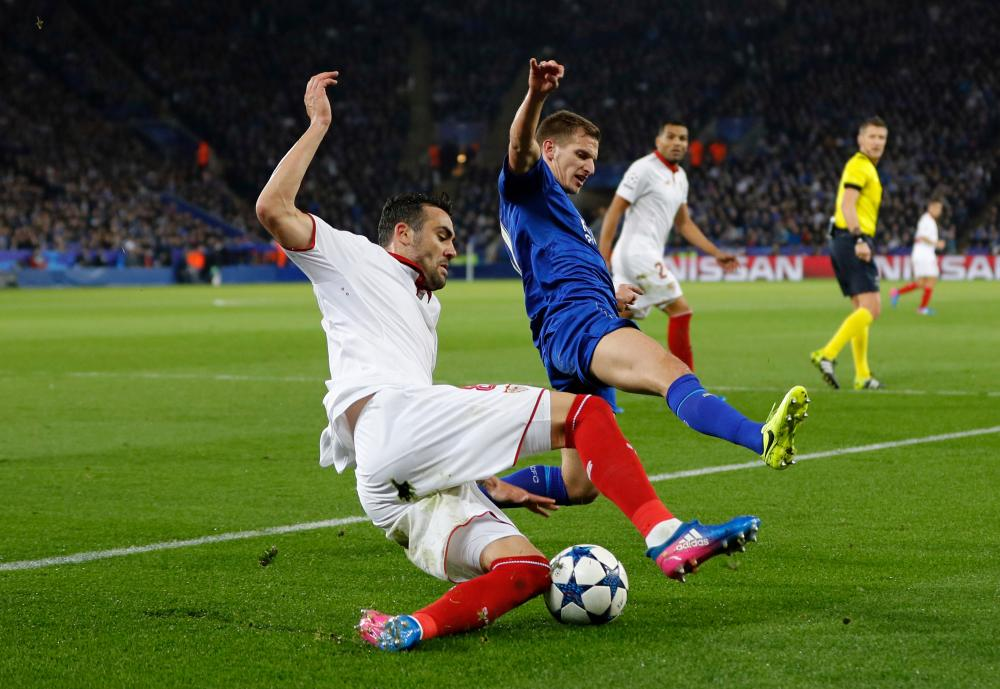 Leicester City's Marc Albrighton attempts to thwart Sevilla's Gabriel Mercado.