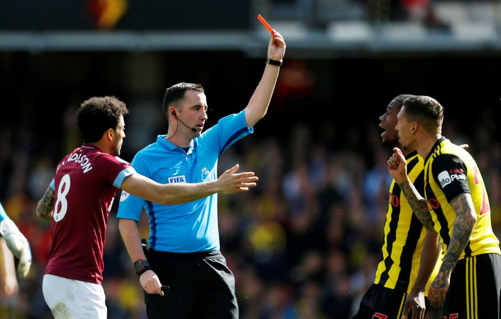 José Holebas is shown a red card by referee Chris Kavanagh.
