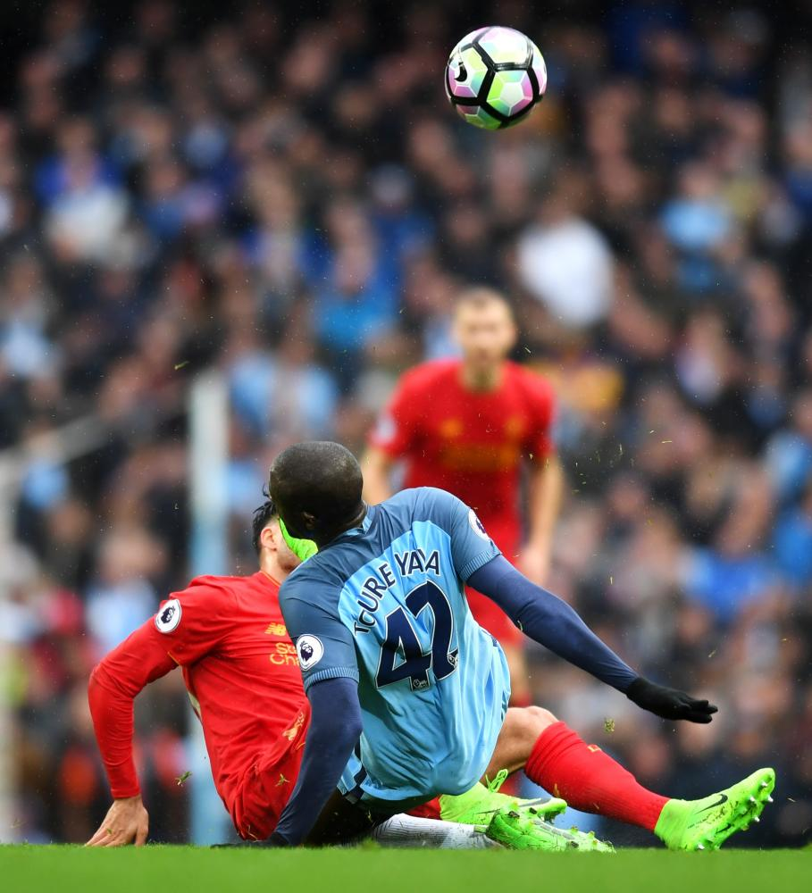 Yaya Toure of Manchester City (R) challenges Emre Can of Liverpool which resulted in a yellow card for the Ivorian