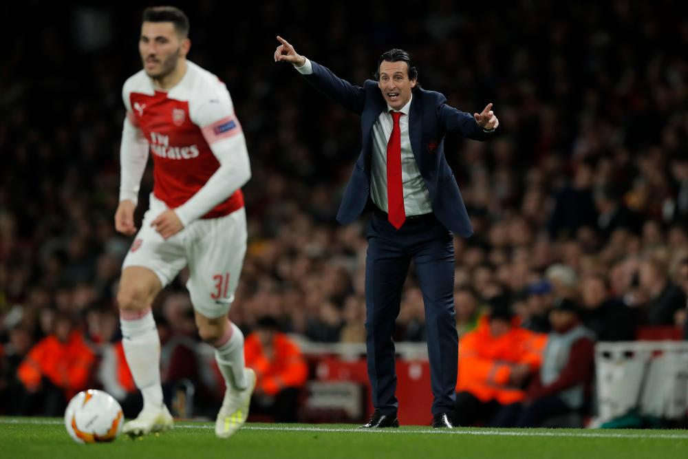 Arsenal manager Unai Emery urges his players forward as Sead Kolasinac carries the ball.