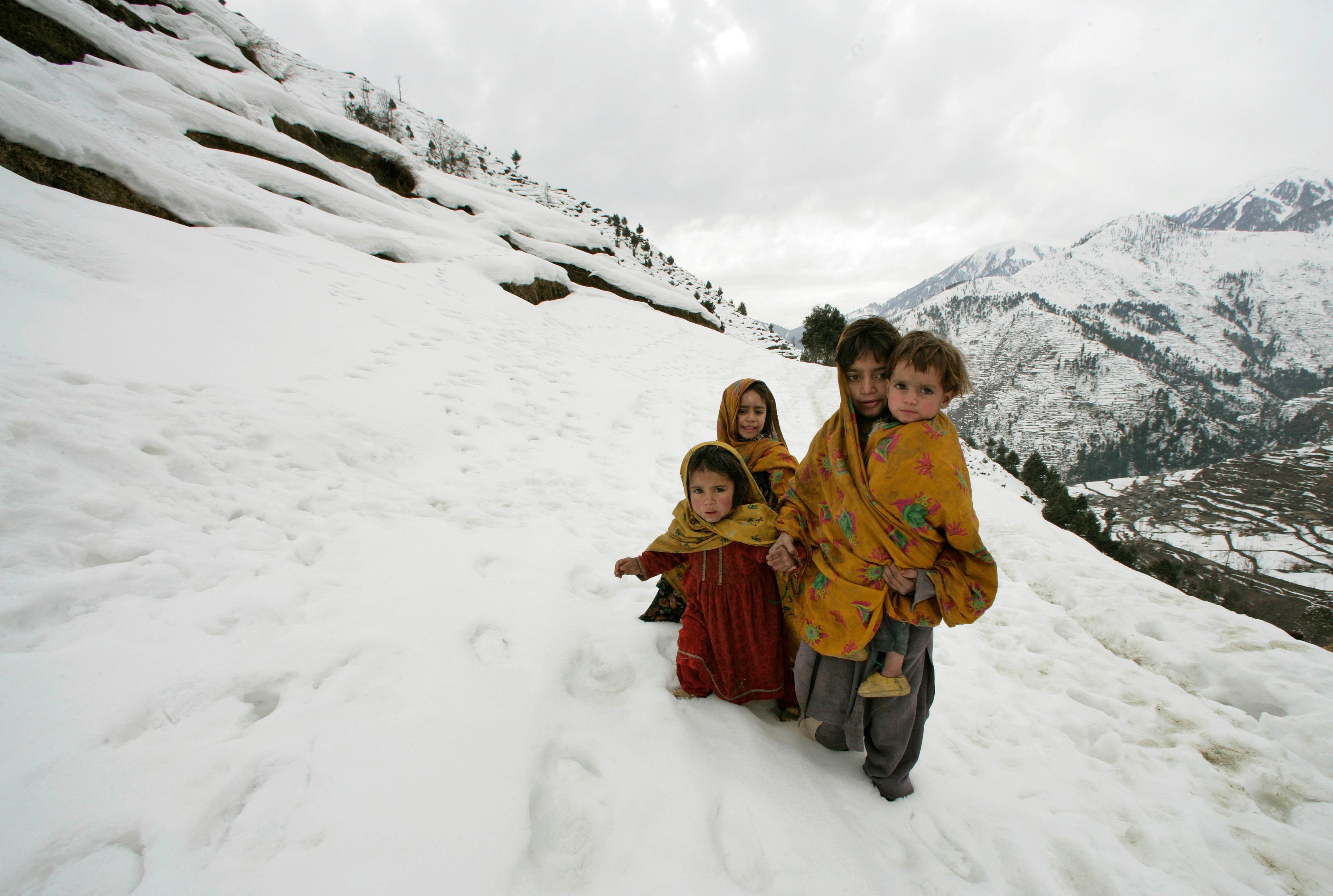 Buy a Guardian classic photograph: Girls walk in the snow, Pakistan, 2006