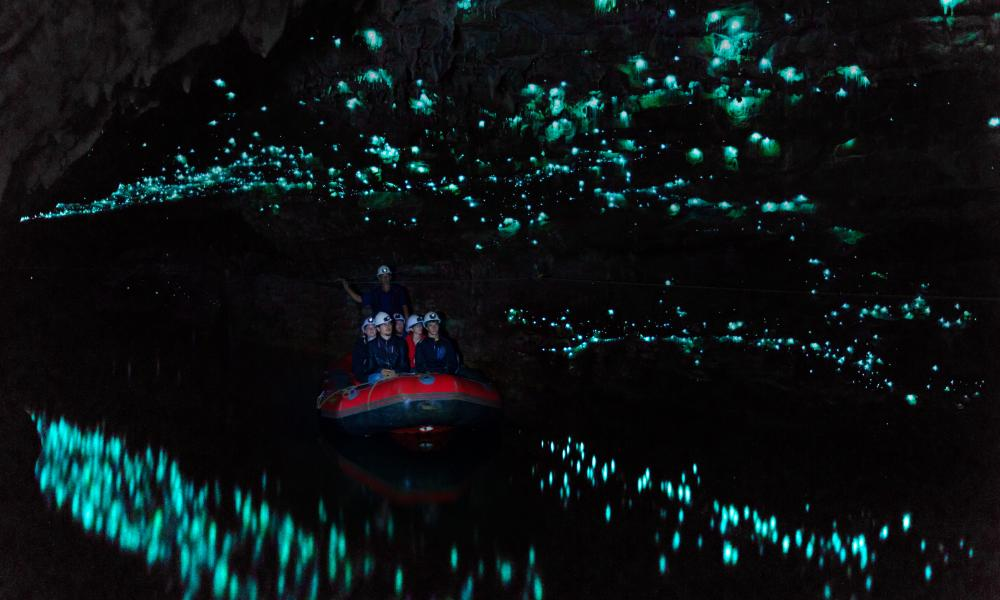 Tourists looking at glowworm cave, Waitomo caves, New Zealand.