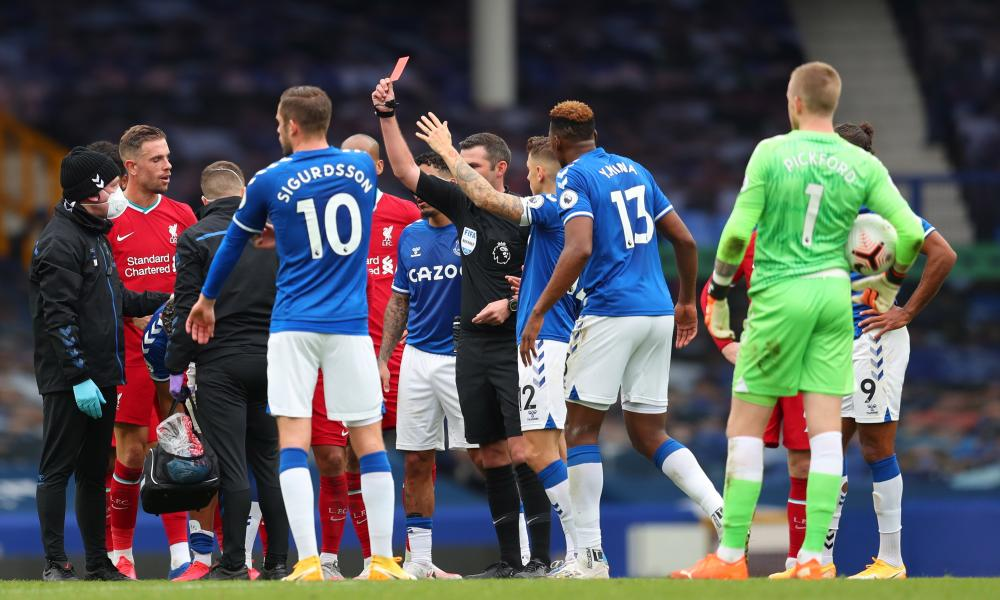 Referee Micheal Oliver shows a red card to Richarlison