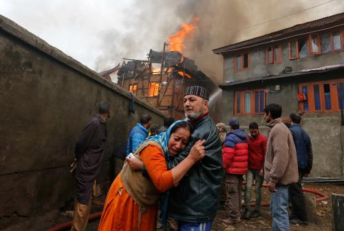 A woman is consoled by a relative after seeing her house ablaze in Srinagar, Kashmir