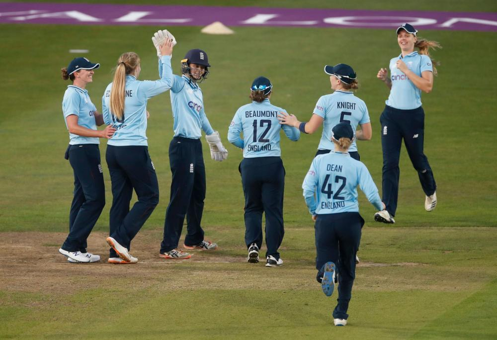 England's Sophie Ecclestone celebrates with teammates after taking the wicket of New Zealand's Katey Martin.