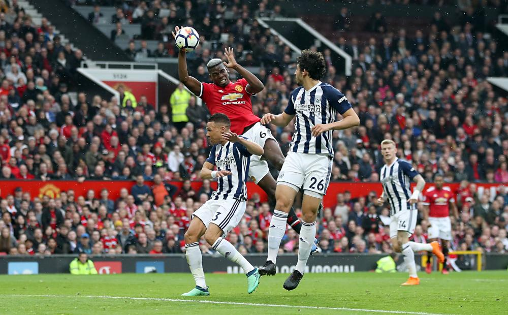 Pogba handles the ball.
