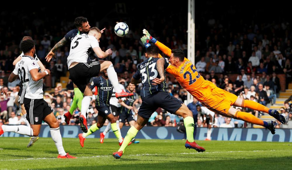 Fulham's Sergio Rico and Calum Chambers combine to put off Manchester City's Nicolas Otamendi.