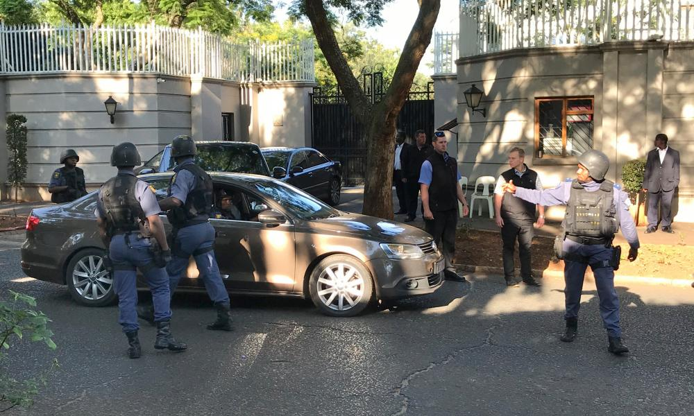 South African police raid the Gupta family compound in Johannesburg.