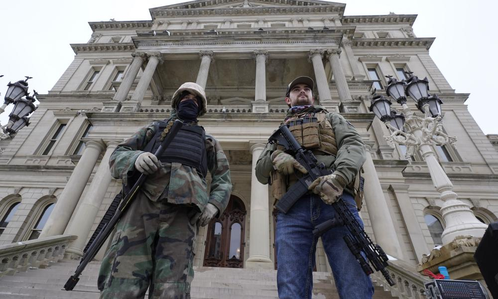 Armed men stand on the steps at the Michigan state capitol after a rally in support of President Donald Trump in Lansing on 6 January 2021.