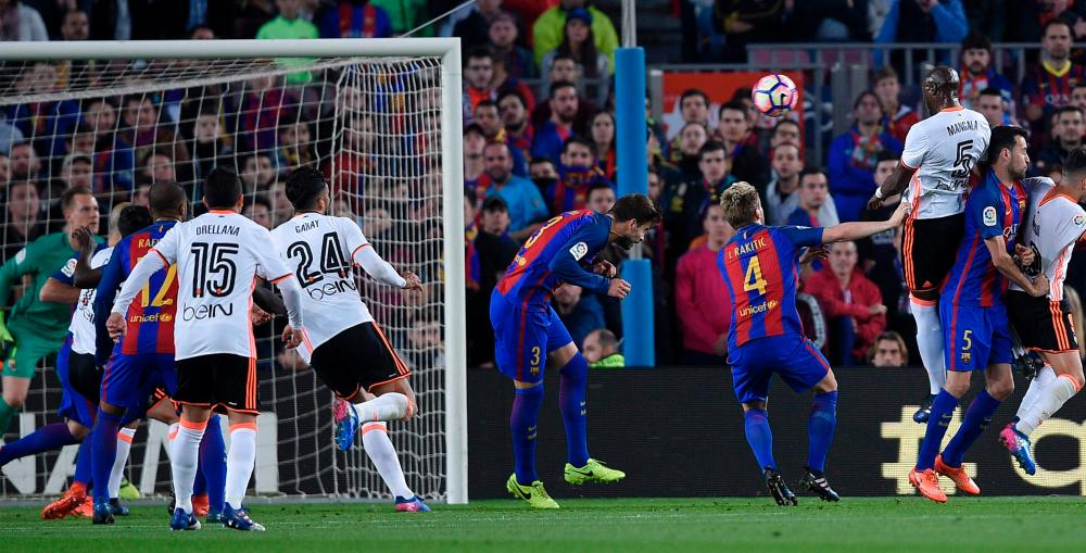 Valencia's Brazilian defender Eleaquim Mangala (R) scores during the Spanish league football match FC Barcelona vs Valencia CF at the Camp Nou stadium