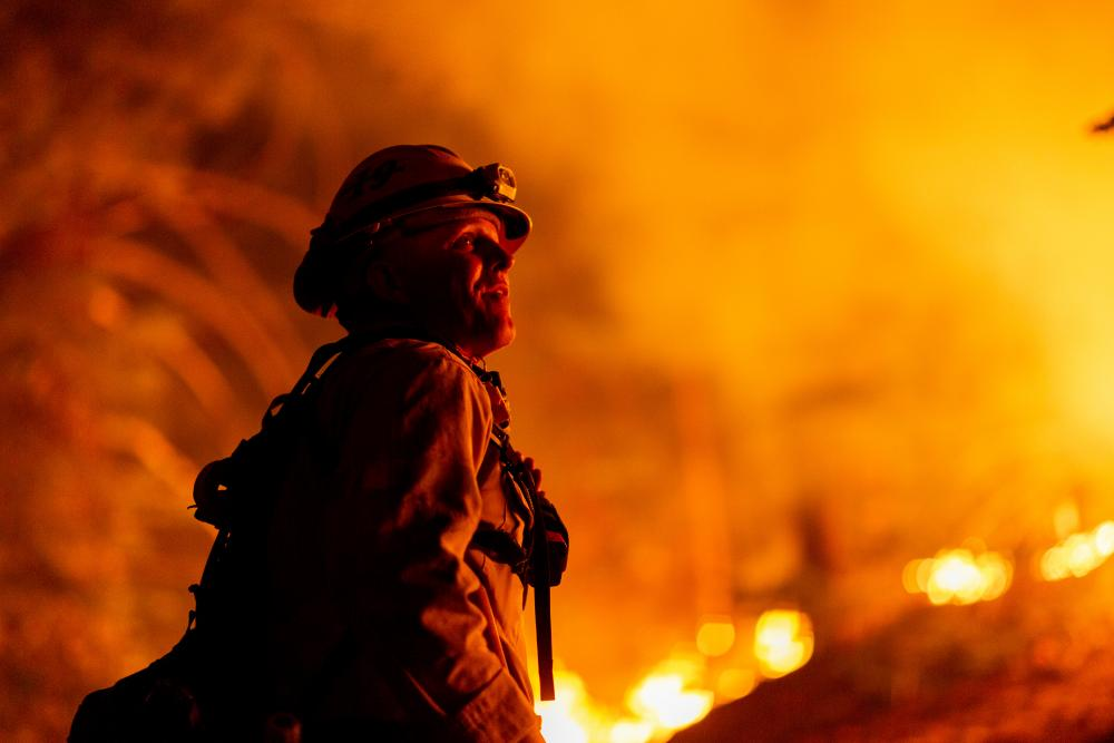 Los Angeles county firefighters use only hand tools to keep fire from jumping a fire break in Angeles National Forest on 11 September.