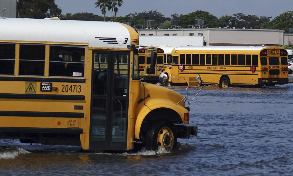 A school bus drives through the flooded parking lot of the Browad School District Central Depot in Oakland Park.