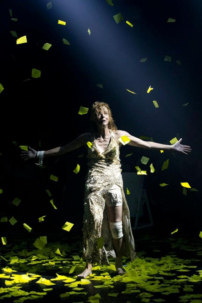 Heather Mitchell on stage surrounded by yellow confetti
