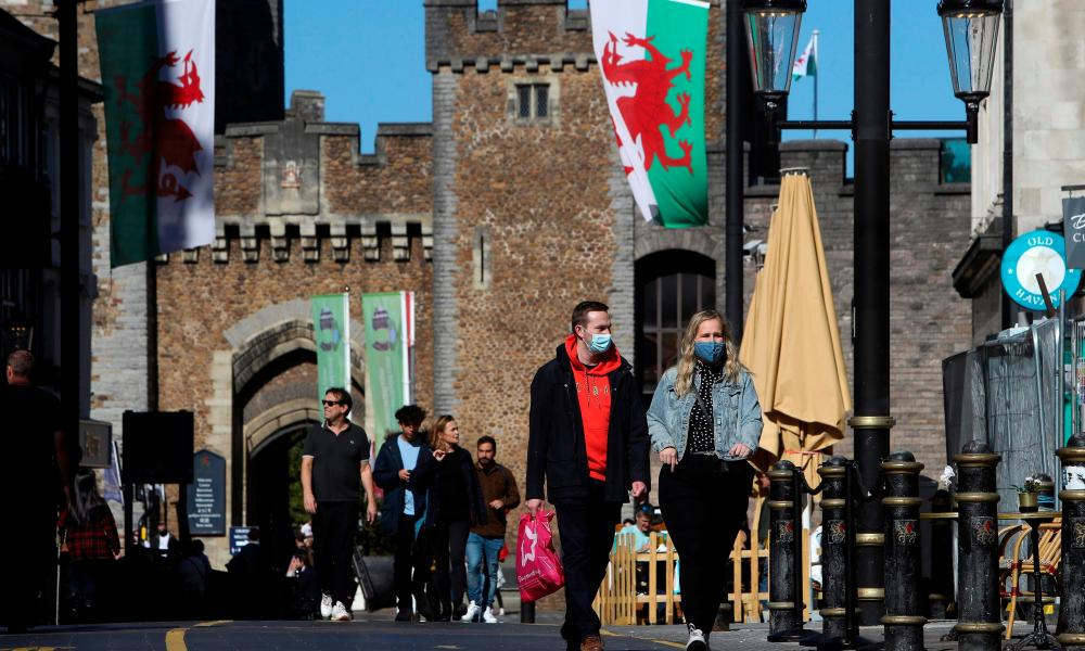 A couple wearing protective face coverings, walk through the city in the late summer sunshine in Cardiff, south Wales on September 27, 2020, during preparations for the reinstatement of a lock-down, ahead of a 6pm deadline.