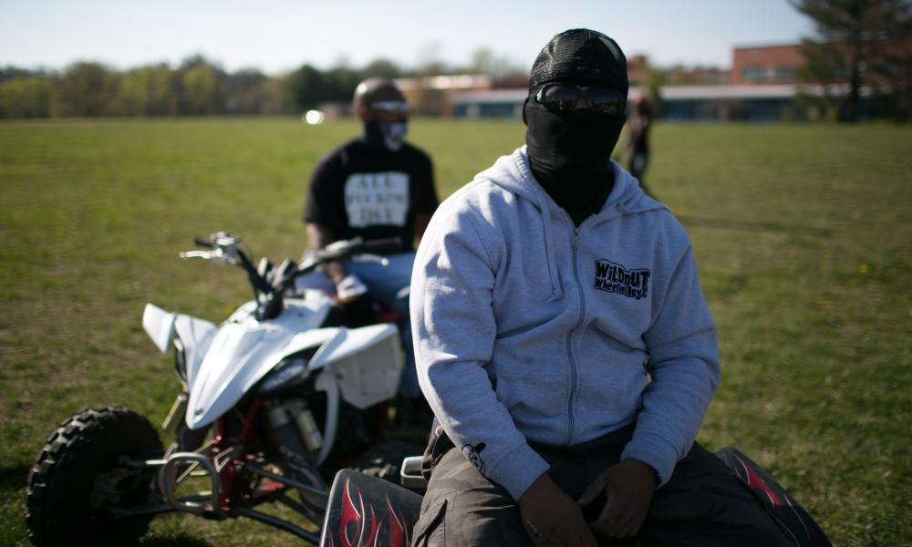 Masked to protect his identity, a WildOut Wheelie Boy waits for the pack to arrive