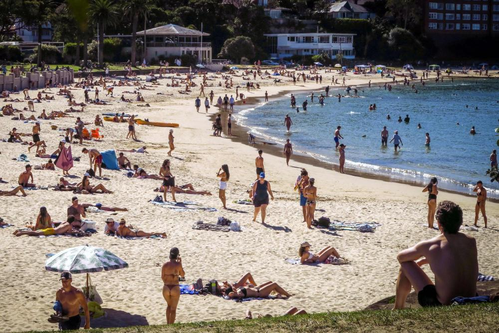 Beachgoers sit and swim at Balmoral Beach amid ongoing social restrictions.