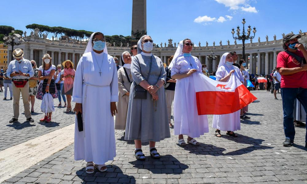 Nuns wearing a face mask, some holding Poland's national flag (R) attend the Pope's weekly Angelus prayer at St. Peter's square in the Vatican on 21 June.