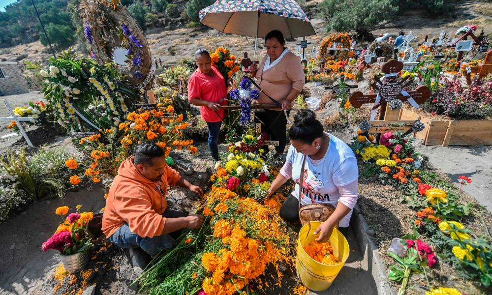 People decorate a relative's grave prior to the Day of the Dead at the Municipal Pantheon in Valle de Chalco, Mexico.