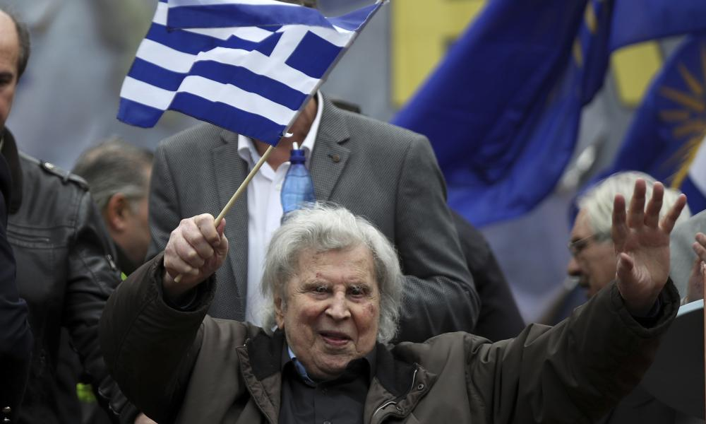 Theodorakis in old age, holding both hands up to salute the crowd, with a blue and white Greek flag on a stick in one hand