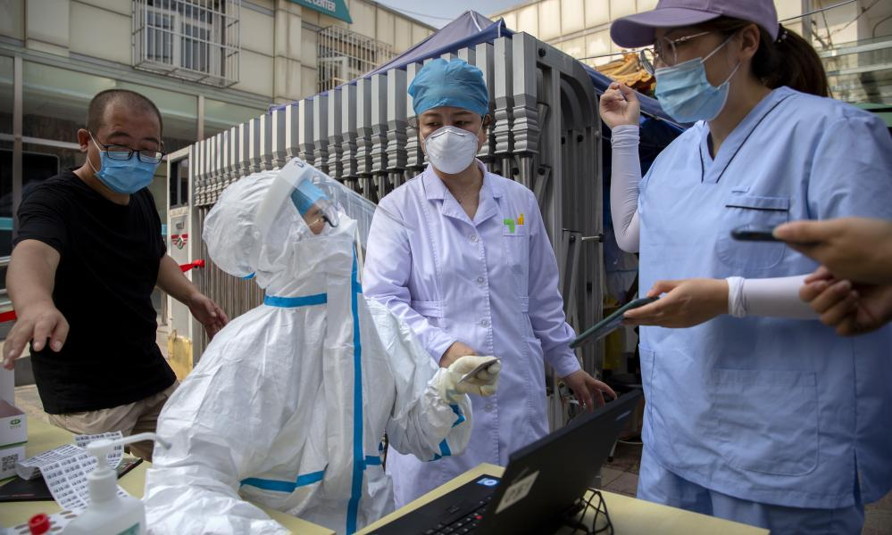 A worker wearing a protective suit talks with people registering for coronavirus tests at a community health clinic in Beijing, Sunday, 28 June 2020.