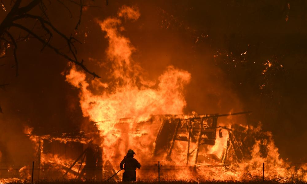 A firefighter tackles a wall of flames