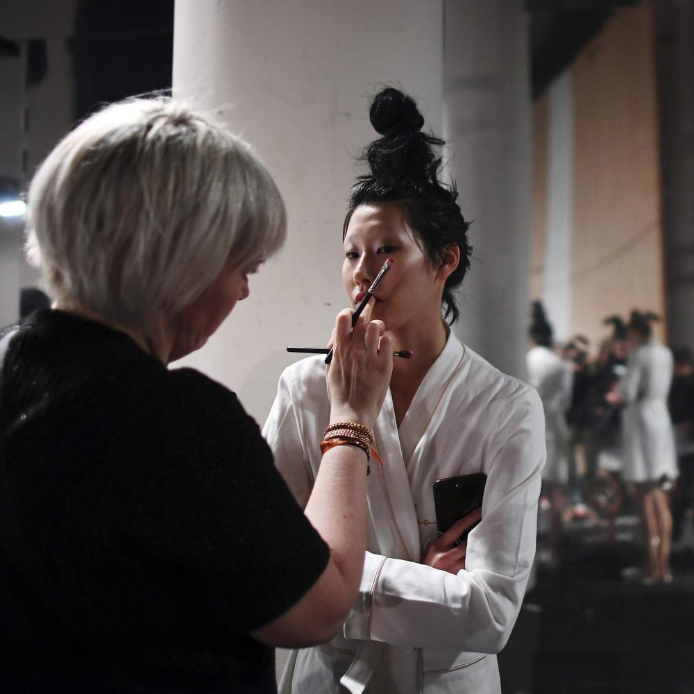 A model has her makeup done before the Guo Pei show