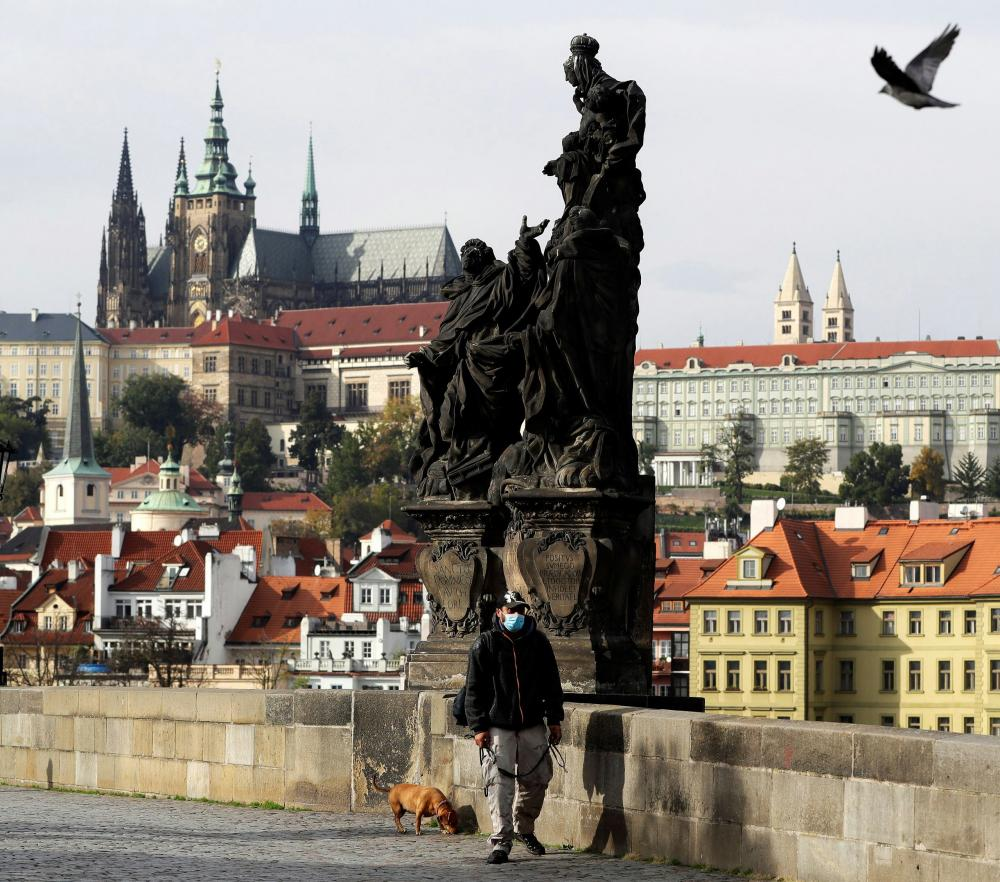 A man wearing a face mask walks his dog across the Charles Bridge, as the spread of the coronavirus disease continues in Prague.
