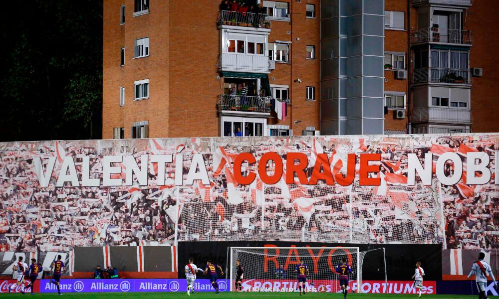 Residents of a building adjacent to the Vallecas stadium stand on their balconies to watch Rayo Vallecano v Barcelona.