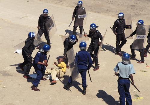 Riot police surround a protester during a demonstration against the introduction of bond notes by the Reserve Bank of Zimbabwe