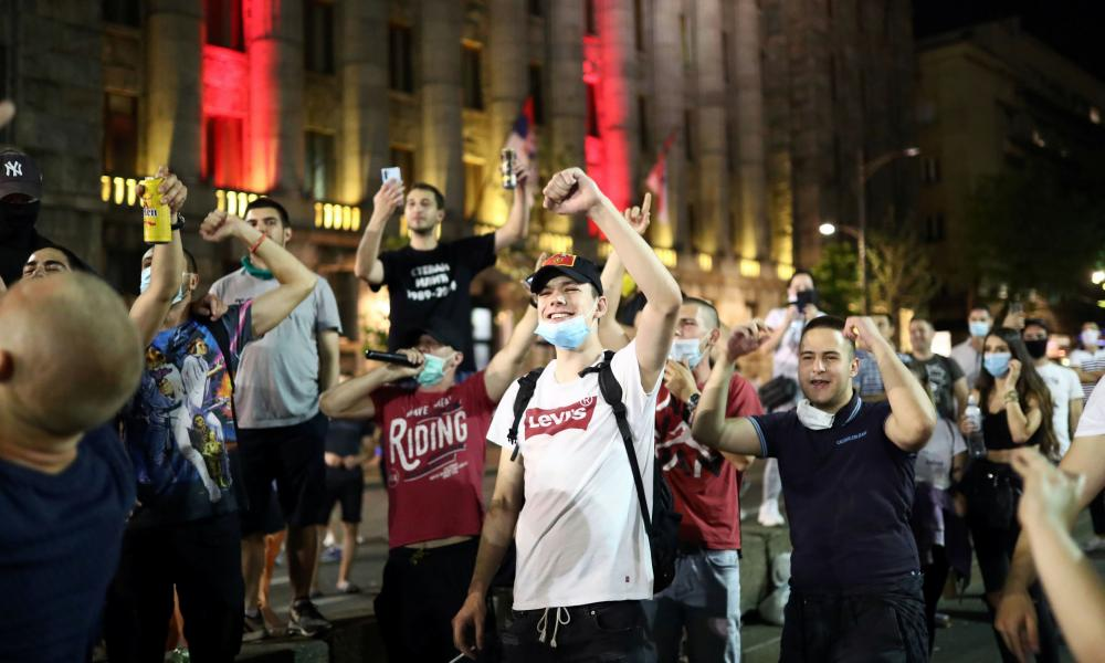 People sing after a rally against the government's lockdown measures, amid the spread of coronavirus, in front of the parliament in Belgrade, Serbia.