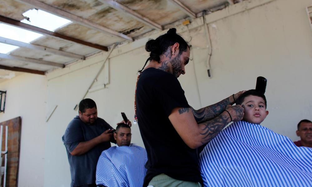 People cut hair in an improvised outdoor barber shop after a business was damaged by the passing of Hurricane Maria in Toa Baja, Puerto Rico.