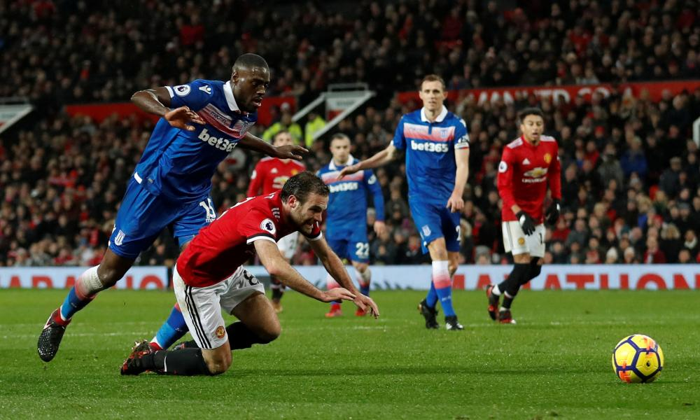 Juan Mata goes down in the area after a challenge by Stoke City's Bruno Martins Indi