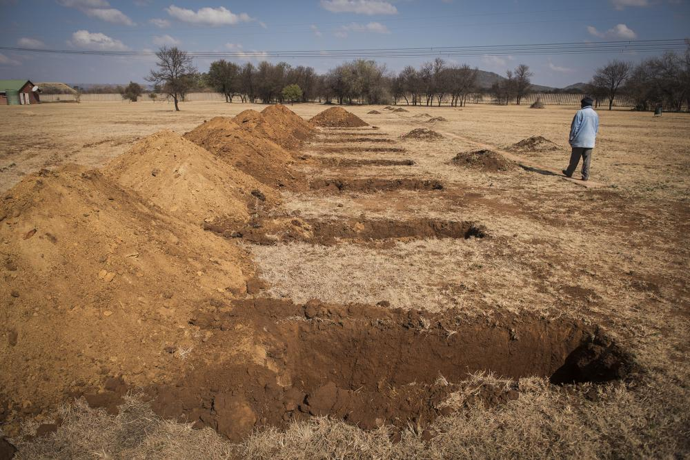 A worker walks past freshly-dug graves at the Honingnestkrans cemetery, north of Pretoria, South Africa.