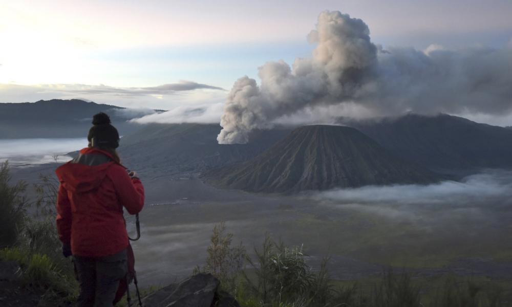 A visitor takes photographs of Mount Bromo