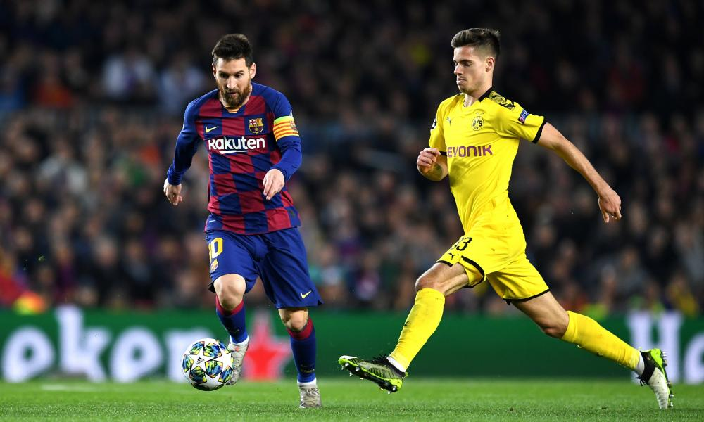 Julian Weigl (right) closes down Lionel Messi during Dortmund's 3-1 defeat to Barcelona last week.