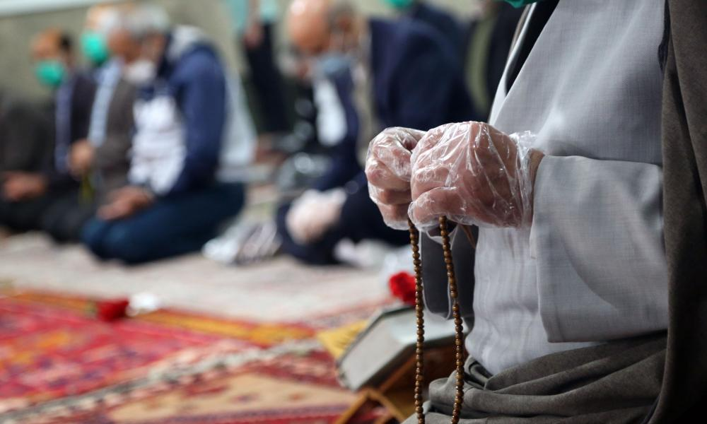 An Imam, wearing gloves, counts beads following a prayer at Imam Sadiq Mosque after Iranian government announced reopening of mosques in low-risk coronavirus areas in Abyek, Qazvin, Iran on 7 May 2020.