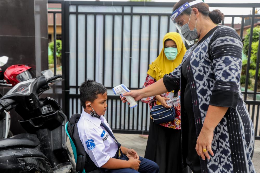A schoolboy gets his temperature measured on the first day of reopening schools in Medan, Indonesia.