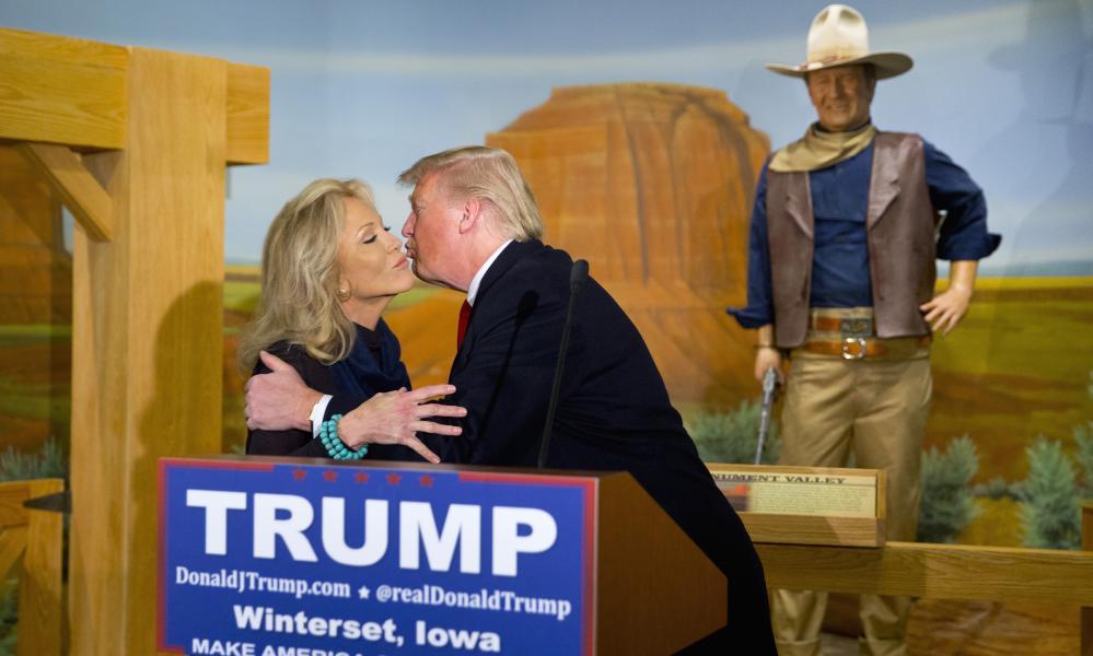 Donald Trump kisses Aissa Wayne as a wax statue of John Wayne watches, in Iowa in January 2016.