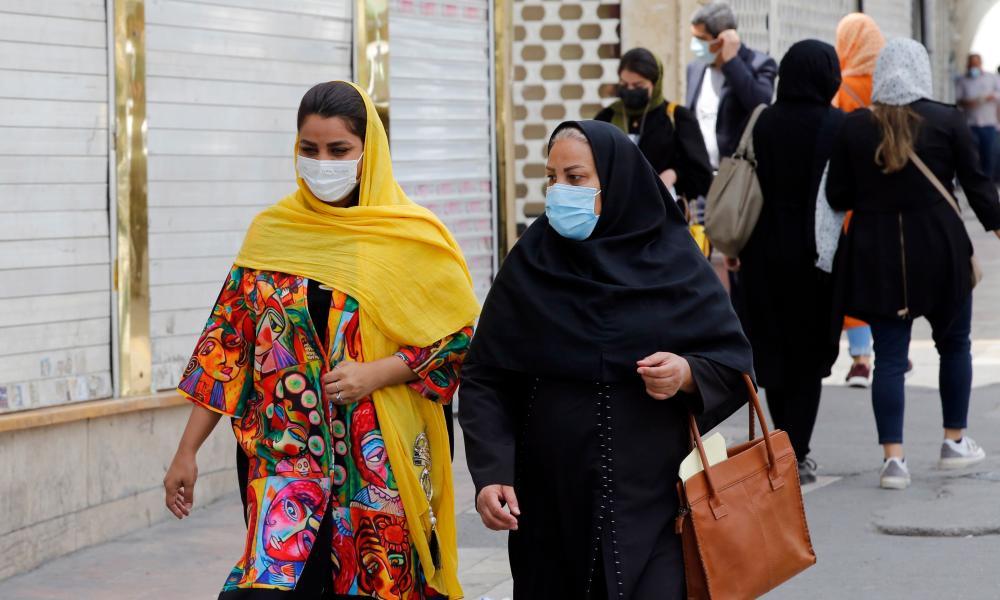 People are seen walking along a street in Iran