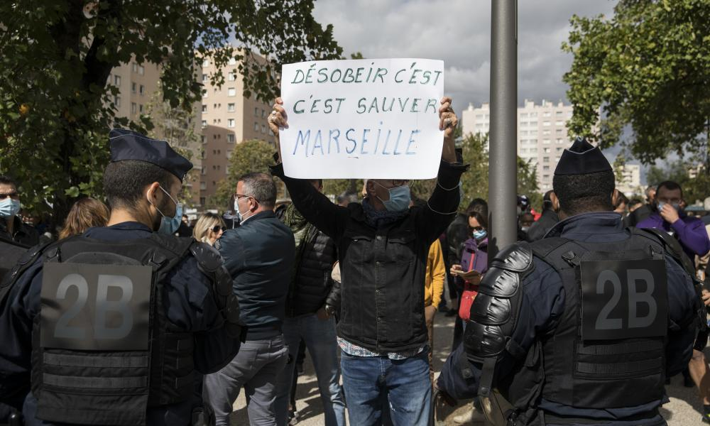 "A restaurant owner holds a sign reading ""to disobey is to save Marseille"" to protest French Health Minister Olivier Veran's visit at La Timone public hospital in Marseille, southern France, Friday 25 September 2020."