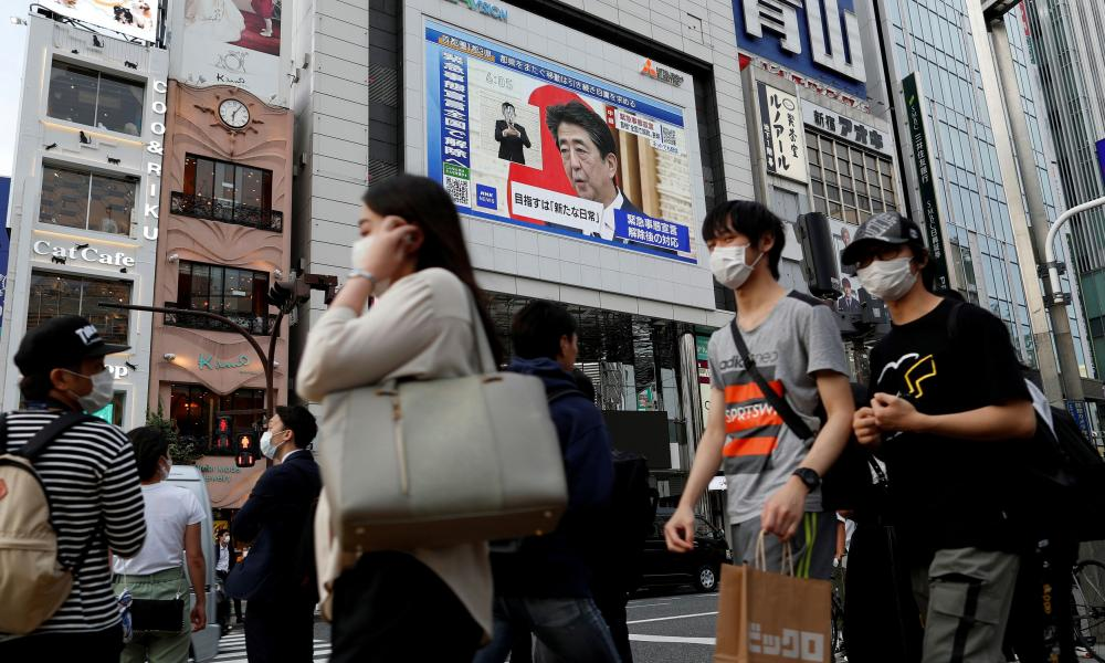 A large screen on a building shows a live broadcast of Japan's Prime Minister Shinzo Abe's news conference at Shinjuku district in Tokyo.