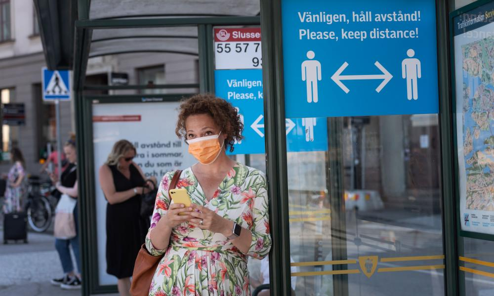 A woman wears a face mask at a bus stop beside an information sign asking people to keep social distance in Stockholm.