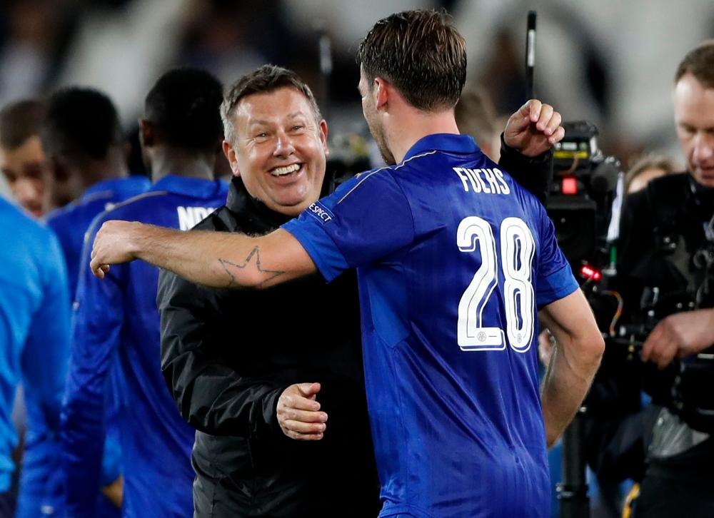 Leicester City manager Craig Shakespeare celebrates with Christian Fuchs after the game.