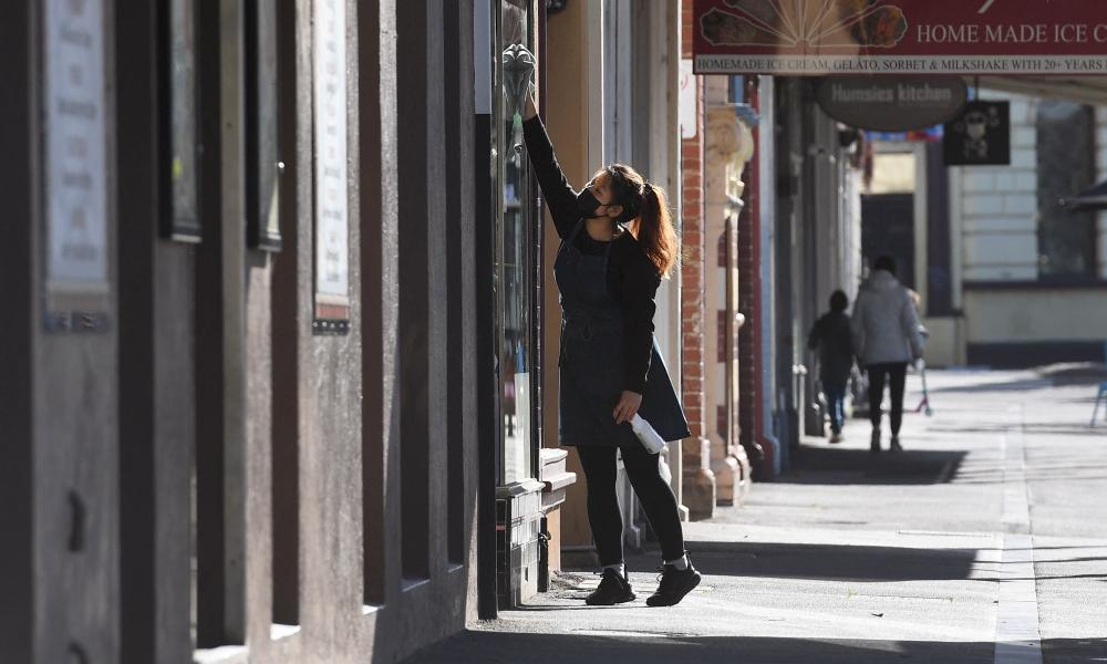A shopkeeper cleans a cafe window on a quiet street in Melbourne on August 25 amid the city's lockdown.