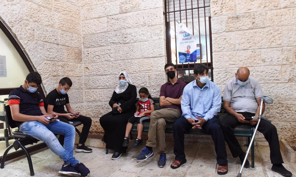 Palestinians wait to receive a Covid-19 booster vaccine in East Jerusalem.