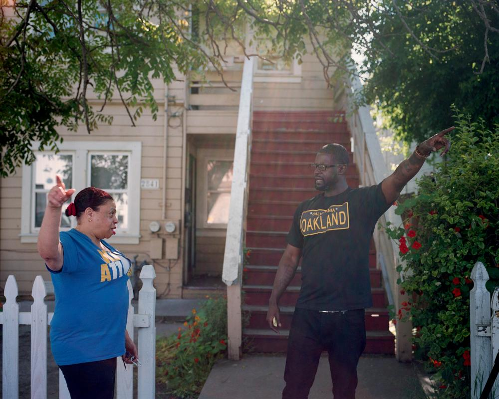 Clarke talks with West Oakland resident Elsie Bell about how the neighborhood has gentrified.