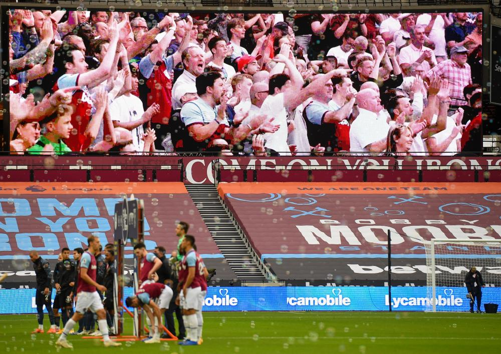 Hammers fans are pictured on a giant screen in the empty stadium as the players line up ahead of kick off.