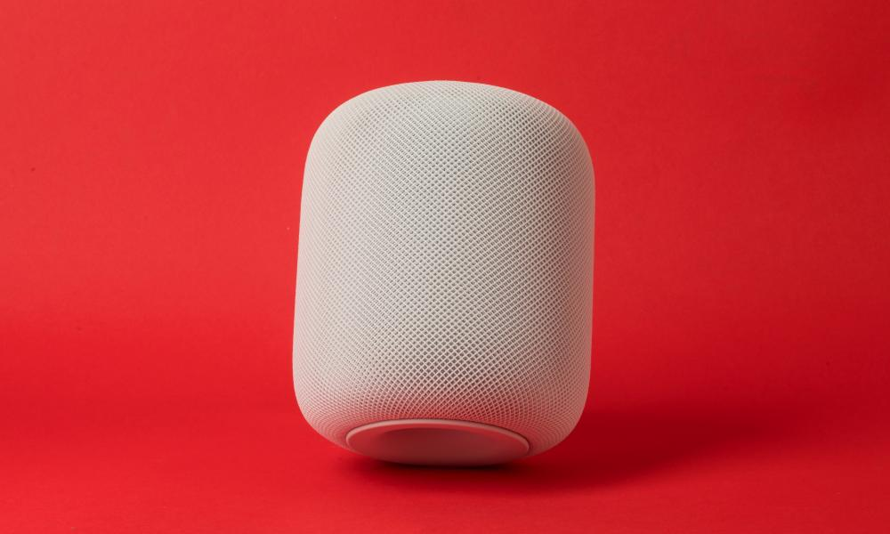 an apple homepod tilted at a slight angle against a red background