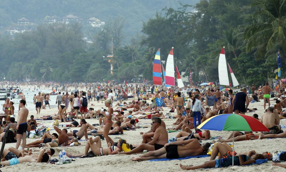 Foreign tourists sunbathe at Patong beach, Phuket island, southern Thailand.