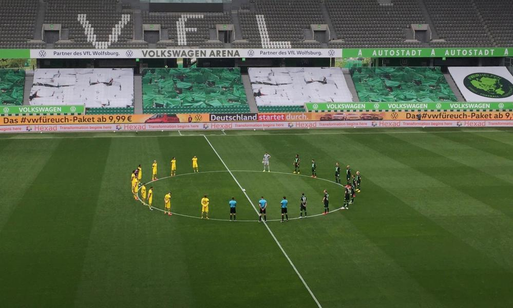 Dortmund and Wolfsburg players stand on the centre circle for a minute of silence for the victims of COVID-19.